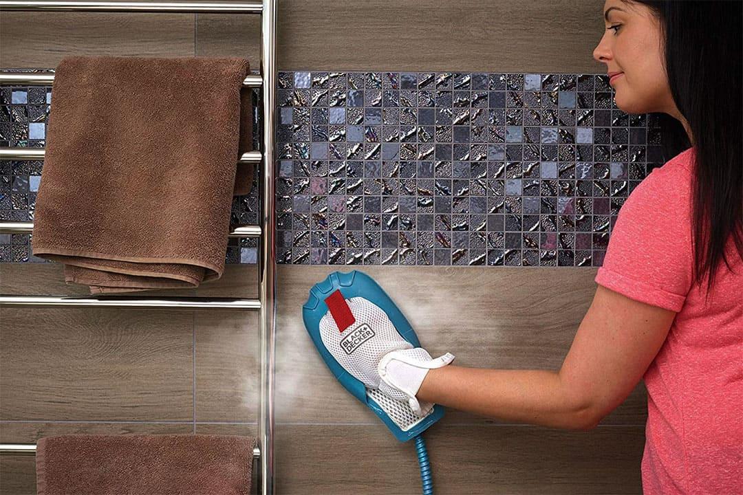 femme nettoie le mur d'une salle de bain